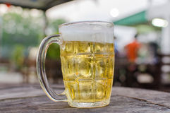 Glass of beer with bar scene in the background Royalty Free Stock Photos