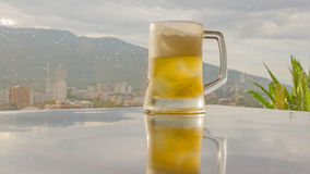 Glass of beer with bar scene in the background. Royalty Free Stock Photography