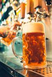 Glass of beer with barrel, bottle and fresh hops still-life. We meet oktoberfest. Hand of bartender pouring a large lager beer in tap. Pouring beer for client Royalty Free Stock Images