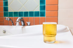 Glass of beer on bathtub Royalty Free Stock Photos