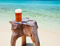 Glass of beer on a beach Royalty Free Stock Image