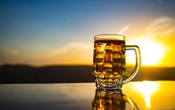 Glass of beer on a beach at sunset. Cooling summer drink concept. Close Up of A Glass of Draught Beer with the Bokeh of Sunlight royalty free stock photo