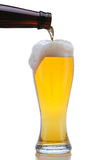 Glass of Beer Being Poured. From Bottle with Foam Drip and Reflection isolated on white Royalty Free Stock Image