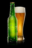 Glass of beer on black. Green Bottle of beer with ice crystals and glass of beer on black background Stock Photos