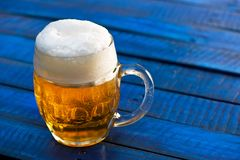 Glass of beer. On the blue wooden background stock photos