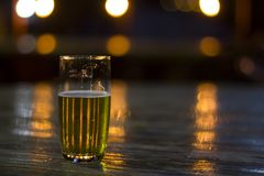Glass of beer with blurred lights on background royalty free stock image