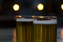 Glasses of beer with blurred lights on background stock image