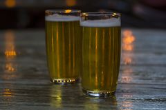 Glasses of beer with blurred lights on background royalty free stock image