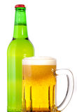 Glass of beer with bottle. A glass of beer in the front with foam with a bottle of beer in the back Royalty Free Stock Photo