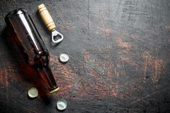 Glass beer bottle and opener. On dark rustic background royalty free stock photo