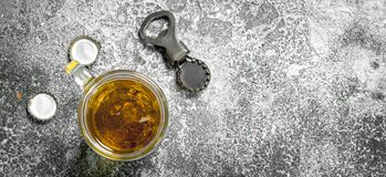 Glass of beer with a bottle opener and stoppers. On a rustic background stock photography