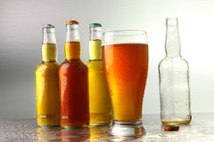 Glass of beer with bottles Stock Photography