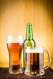 Glass of beer with bottles Royalty Free Stock Photography