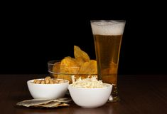 Glass of beer, bowl with chips, squids, pistachios Stock Photos