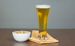 Glass of beer, bowl with pistachios Royalty Free Stock Photo