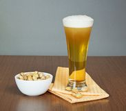 Glass of beer and bowl with pistachios Royalty Free Stock Image