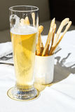 Glass of beer and bread sticks on table Royalty Free Stock Image