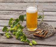 Glass of beer and brown bread with sprats on a wooden table Stock Photo