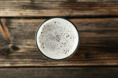 Glass of beer on brown wooden background. Royalty Free Stock Photography
