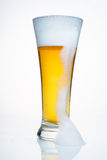 A glass of beer with a cap of foam. With a large drip foam. A glass of beer with a cap of foam. With droplets of condensate, with a cap of foam and a large drip Stock Photo
