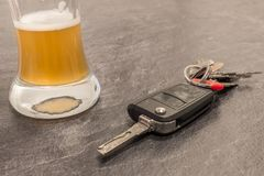 Glass of Beer and car key on grey table Royalty Free Stock Photography
