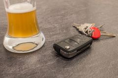Glass of Beer and car key on grey table Stock Images