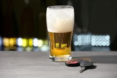 Glass of beer and car keys. On grey table royalty free stock photos