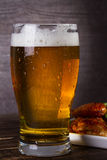 Glass of beer and chicken wings on dark wooden background. Stock Photo