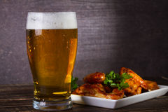 Glass of beer and chicken wings on dark wooden background. Stock Photos