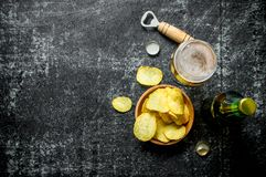 Glass of beer and chips in the bowl. On rustic background stock images