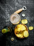 Glass of beer and chips in the bowl. On rustic background royalty free stock photos