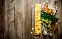 Glass of beer and chips on wooden table. Stock Image