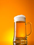 Glass of beer close-up. With froth over orange background Stock Photos