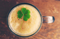 Glass of beer with clover leaf on wooden background. Royalty Free Stock Photo