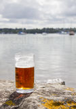 Glass of beer by the coast Stock Images
