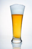 A glass of beer with condensation. A glass of beer with a cap of foam. With droplets of condensate, on white background Royalty Free Stock Images
