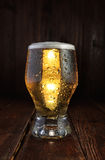 Glass beer on dark wood table. Vertical orientation. Glass cold beer with drops on dard wood table. Vertical orientation Stock Photo