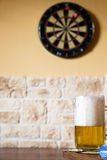 Glass of beer and dartboard Stock Image