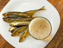 Glass of beer and dried fish on a plate Stock Images