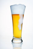 A glass of beer. With the drip of foam. A glass of beer with a cap of foam. With droplets of condensate, with a cap of foam and a large drip foam. On white Stock Photo