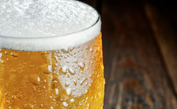 Glass of beer with drops. Close-up. Blurred background. Glass cold beer with drops on dard wood table. Close-up. Blurred background Stock Images