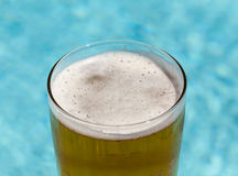 Glass of beer on edge by poolside Royalty Free Stock Image