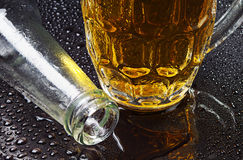 Glass of beer and an empty bottle Royalty Free Stock Photography
