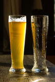 Glass of Beer Beside Empty Glass on Table Royalty Free Stock Image