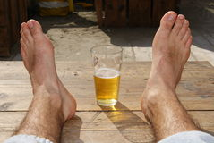 Glass with beer between feet. In sunny day Stock Images
