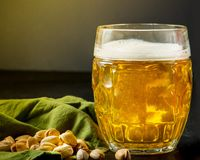 Glass of beer filled to the brim. On a dark background stock images