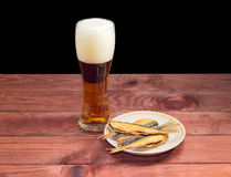 Glass of beer and fish snack on wooden surface Royalty Free Stock Photos