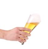 Glass of beer with foam in hand. Royalty Free Stock Photos