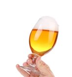 Glass of beer with foam in hand. Royalty Free Stock Photo