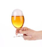 Glass of beer with foam in hand. Stock Images
